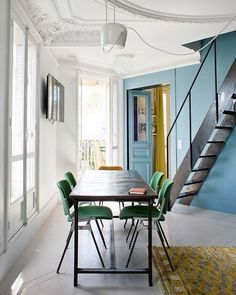 What a beautiful, inspirational interior:  • the coloured wall and door, • the AIM pendant lamp (via TRNK), • the sleek table and chairs, • the green colour of the chairs, • the mustard green rug and how the colour is picked up in the room next door, • the way the modern staircase sits in this classic, historic space, • the fantastic use of an awkward looking space...  Love it!! Via Elysian Spaces.