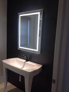 Framed rectangular mirror with lighting integrated directly into mirror.