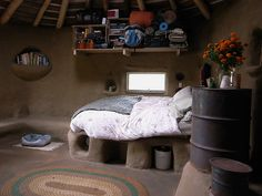 cob bed platform heated by a rocket stove (foreground) with homemade straw mattress in the GOBCOBATRON