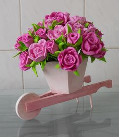 Carriola decorada com mini rosas e mini botões de rosas na cor rosa. Disponibilidade de elaboração com outras flores e cores variadas sob consulta.