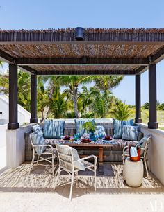 """Scheerer roofed the pergola with bamboo fencing from <a href=""""http://www.walmart.com/"""">Walmart</a>; the stacking armchairs are by <a href=""""http://www.janusetcie.com/"""">Janus et Cie</a>, and the large pillows and the striped <a href=""""http://www.crateandbarrel.com/"""">Crate and Barrel</a> pillows are all of <a href=""""http://www.sunbrella.com/en_us/"""">Sunbrella</a> fabrics."""