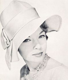 John Frederics recalls the glamour of Garbo in a 1957 version of the swagger hat. Fashioned of beige balibuntal straw, it has a tall, indented crown, and a profile rippling brim, accented with a wide band of matching beige satin, Crystal necklace by Marvella. #passion4hats