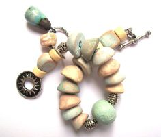 Most of the beads in this bracelet are made by a woman named Nadia in Bulgaria. Her shop on Etsy is NadiaTerra. Her work is so unique. These are all ceramic, made without glaze. Rustic and super lovely! -- Bohemian Ceramic Bracelet Unusual Rustic Pastel & by SheFliesAgain