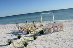 2 post Bamboo Arbor with champagne colored chair sashes.  Photo and set-up by Sunset Beach Weddings.