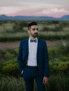 Navy blue suit + suspenders + a botanical bow tie | Image by John David Weddings