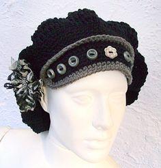Boina tramada em crochê com aba e caimento atrás adornada com botões nas cores preto e cinza chumbo.  O broche flor é feito em renda com botão biju metalizado,
