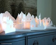 DIY - Paper cut Winter Village. This winter village has a mountain scape in the background with little village houses, clock towers, light poles and trees in the front two layers. The cut also features a bridge and deer, a rabbit and fox.: