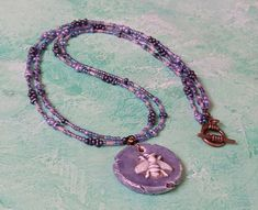 This delicate necklace has been made with a double length of beading wire threaded with a mix of seed beads in shades of pinks, purples and blues. The pendant is a purple-blue ceramic disc with a raised bee in white. A copper toggle clasp has been used. Seed Bead Necklace, Seed Beads, Washer Necklace, Beaded Necklace, Organza Gift Bags, Handmade Jewellery, Purple, Pink, Seeds
