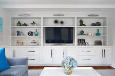 A large white built-in serves as the perfect entertainment center in this calming living room. This convenient entertainment center offers both shelves for books and decor and lower cabinets to hide electronics and cords.
