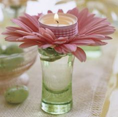 Shot glass, live Gerber daisy with stem removed and a tea light wrapped with ribbon placed on top.