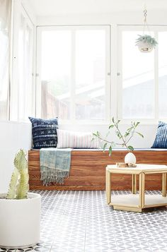 Sunroom boasts a built-in window seat bench lined with dark blue pillows facing…
