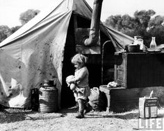 Depression, Dorothea Lange - Little girl, daughter of fruit tramps outside tent she shares with her parents and four siblings. CA 1936