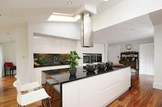 High gloss white cabinets, black granite wraparound worktops, walnut floor, Elica extractor