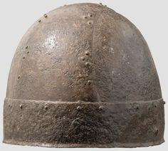 Iron banded helmet, Central Europe, Migration Period, 5th/6th centuries A.C. The skull worked in one piece with rivets arranged in groups of three. Damaged area on the crowns apex about 2 cm wide. A circa 5 cm broad riveted band runs around the lower rim. Holes on the sides for the missing chin straps or cheek-pieces, 16.5 cm. Private collection, from Hermann Historica auction