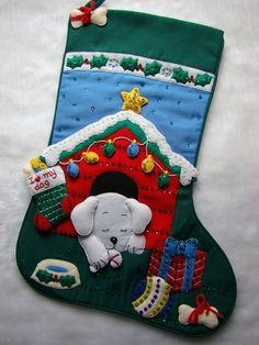 "Bucilla~This wonderful 21"" Christmas Stocking called ""PUPPY'S CHRISTMAS"" is made of felt applique on cloth and beautifully decorated with hand sewn sequins and beads. A cute white puppy is asleep in his house which is deocrated with lights, a star and stocking. Outisde the dog house is a gift, food bowl, ball and bone. The top of the stocking has a bone in the corner and a place to embroider your puppy's name."