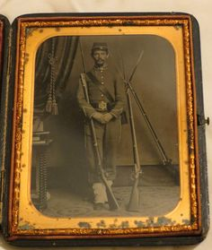 Tintype in Case Confederate Soldier standing in frront of stacked arms.