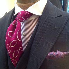 Paul Stuart ~ Men's plum check 3 pc suit, fushia stripe shirt w/ white wingtip collar, graphic tie & paisley lapel scarf.