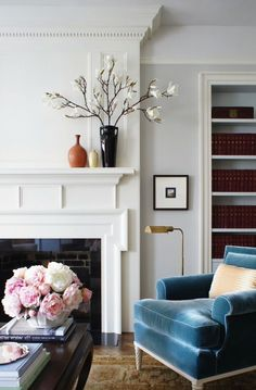 Blue velvet chair in chalky white living room.