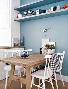 warm wood dining room table with pretty white chairs and serene blue wall and floating shelves.