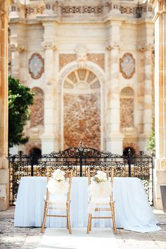 Such a spectacular setting for this Malta destination wedding ceremony with gold chiavari chairs and flowers and tulle on the back of the chairs