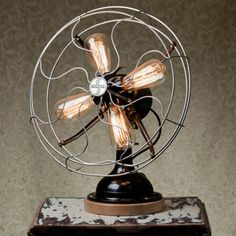 Fan-tastic Lamp by Blinklab. Steam-punk inspired lamp made from a 1939 Signal Fan. Black body, with metal cage, brass fittings, wooden base, & 4 reproduction Edison light bulbs.