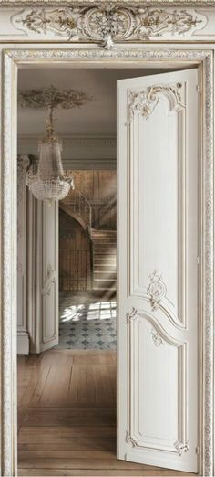 A beautiful example of French country style at its best. The ornate door and beautiful chandelier are pulled into the country by the fantastic wood floor.