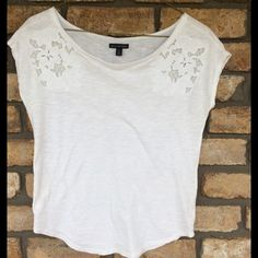 AE White Top White Top, Short Sleeves. Has a Cute flower Lace decoration on the shoulder area. Top is in Great pre-loved condition. American Eagle Outfitters Tops