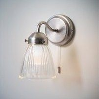 Designed specifically for bathrooms and cloakrooms, our Bathroom Wall Light boasts a charming fluted glass shade and has been brought right up-to-date with its nickel finish. With a swan neck adding curve appeal this is a wall-mounted light that would suit both traditional and contemporary bathrooms. There is a pull cord to switch on/off if desired or alternatively leave it pulled on and operate with the main lightswitch as normal.