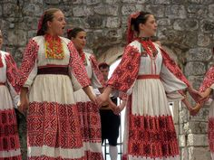 People from Moslavina, a region in Croatia that encompasses Zagreb, traditionally wore white clothing heavily embroidered with geometric designs. Panels of embroidery decorate the sleeves and skirts of these Croatian dancers. The women wear coral necklaces, though other types of neckwear is also typical to this region