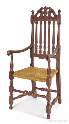 Pook & Pook. April 25th 2014. Lot 9. Boston William & Mary painted armchair, ca. 1730, with a carved crest & banister back. Rush seat & baluster & block turned legs joined by stretchers. Exceptional paint history with an old red over an earlier red & the original black surface.  Estimated: $10K - $20K