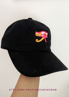 Show off your sense of style with a colorful embroidery of the Egyptian Eye of Horus. The embroidery is intricate with lots of details and placed onto our pure cotton baseball cap. The Eye of Horus is known to provide protection for its wearer. Pair this cap with your everyday outfit and look super cute and put together effortlessly.ou are sure to receive lots of compliments with this eye-catching baseball hat. #baseballhat #baseballcap #dadhat #streetstyle #EyeofHorus #embroiderycap