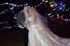 Mrs. Sunhat's New Year's Eve winter wedding couple portraits - second location pictures.  Veil over the bride and groom in front of Christmas lights.
