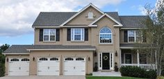 Large home painted with 3 colors;Tan stucco, cream trim and black accents including the front door.