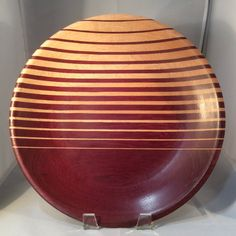 This plate is a purpleheart and maple lamination, 11 & 1/2 in diameter, and 1 & 1/2 high. The smallest strips are 1/16 wide - each successive strip is 1/32 wider. Finished with food safe oil and buffed with carnauba wax.