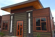 Warm Espresso and Tamarack Green Lap Siding on beautiful commercial building. Also featuring real wood ceiling paneling in the soffit areas.