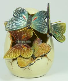 SERGIO BUSTAMANTE CERAMIC BUTTERFLY EGG  Sergio Bustamante ceramic egg depicting butterflies emerging from a cracked egg. Signed Sergio Bustamante to lower right.