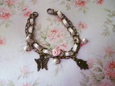 Pulsera cadena bronce con cinta perla, flor de cinta y dijes metal. https://www.facebook.com/pages/Nanoja/100973873394780