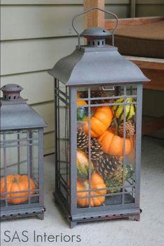 Lantern w fall gourds, pinecones,etc. sitting in corner of porch.