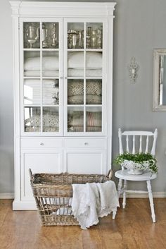 White glass fronted linen cupboard - would have less trim but some wainscoting panelling and also a hidden laundry basket in bottom section for used towels and space for cleaning products / loo rolls etc