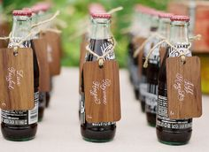 Wood place cards on coke bottles at wedding