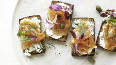 These healthy toasts boast herb-inflected goat cheese, smoked salmon, bitter greens, thinly sliced red onion, and briny caper berries as toppings. Turn to 10 Better-than-Jelly Ideas for Sliced Bread for more open-face snack ideas. Quick And Easy Appetizers, Easy Appetizer Recipes, Snack Recipes, Vegan Appetizers, Smoked Salmon Recipes, Seed Bread, Tostadas, Yummy Snacks, Clean Eating Snacks