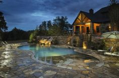 Elaborate swimming pool with dry-laid stone retaining walls, flagstone patios and beach entry, with a natural boulder waterfall.
