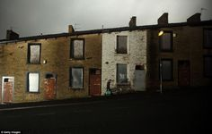 Bleak: A lone woman walks through the empty streets of Woodnook, Accrington. Developers hope that these streets will soon be bustling with a project underway to create four-bedroomed homes fit for the 21st century family
