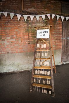 Escort cards displayed on a rustic old ladder... great idea for pretty wedding chic.
