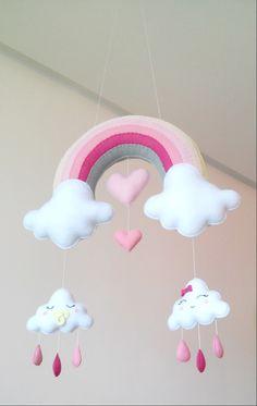 Móbile feito de feltro, costurado a mão e preenchido com fibra siliconada.    Lindo móbile composto por um arco-íris, nuvens fofinhas e corações. Sua leveza, o seu colorido e mobilidade traz calma e distração para o seu bebê.    Deixa qualquer ambiente alegre e divertido.    Medidas Aproximadas: ... Baby Crafts, Felt Crafts, Diy And Crafts, Baby Shawer, Baby Toys, Felt Ornaments Patterns, Little Pony Birthday Party, Hanging Mobile, Floral Baby Shower