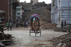 A man pedals a Nepalese cycle rickshaw past damaged buildings at the Basantapur Durbar Square in Kathmandu on April 26, 2015.