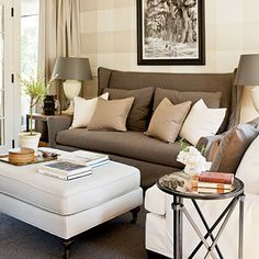 A neutral seating area with a brown loveseat, white upholstered ottoman, white armchair and round metal side table