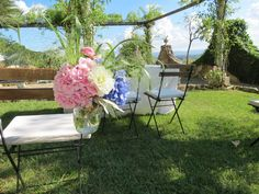 Glass jar for the chairs with pink and blue hydrangea, white dahlia and greenery. Event Planner : Wedding Italy.