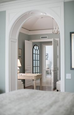 An elegantly trimmed arch connects the grand foyer with the living