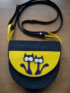 A small bag with cats on it, made almost entirely with felt.